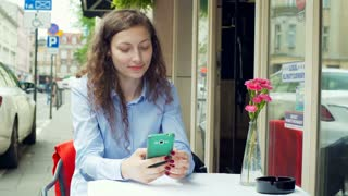 Pretty girl sitting in the cafe and texting sms on smartphone