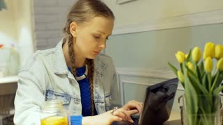 Pretty girl sitting in the cafe and typing something on laptop