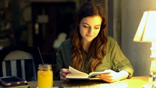Pretty girl sitting in the cosy cafe at night and reading book