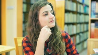 Pretty girl sitting in the library and smiling to the camera