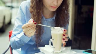 Pretty girl sitting in the outdoor cafe and eating cream from latte, steadycam s