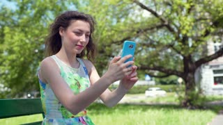 Pretty girl sitting in the park and doing selfies on smartphone