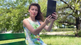 Pretty girl sitting in the park and doing selfies on tablet