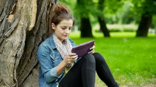 Pretty girl sitting in the park and playing a game on tablet