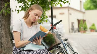 Pretty girl sitting next to her bicycle and reading a book