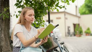 Pretty girl sitting next to the bicycle and drawing in her sketchbook