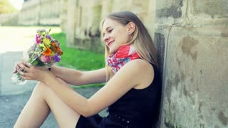 Pretty girl sitting on pathway and holding bunch of colorful flowers