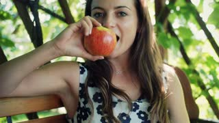 Pretty girl sitting on the bench and eating tasty apple