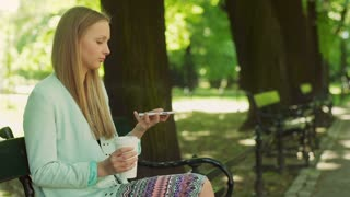 Pretty girl sitting on the bench in the park and doing selfies on smartphone