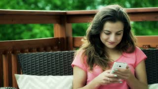 Pretty girl sitting on the deck and texting on smartphone