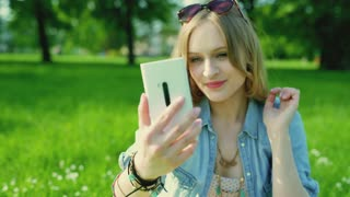Pretty girl sitting on the meadow in the park and doing selfies on smartphone