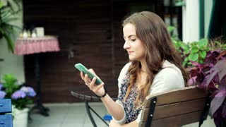 Pretty girl sitting on the wooden chair in the cafe and talking on cellphone