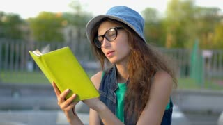 Pretty girl sitting outdoors and reading her journal