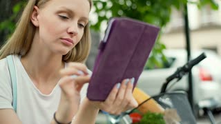 Pretty girl sitting outside and browsing internet on tablet