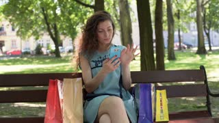 Pretty girl sitting with her shopping on the bench and texting on smartphone
