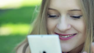 Pretty girl smiling while browsing internet on smartphone