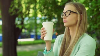 Pretty girl standing in the park and drinking coffee