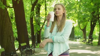 Pretty girl standing on path in the park and drinking coffee
