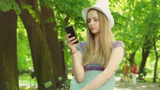 Pretty girl standing on path in the park and using smartphone