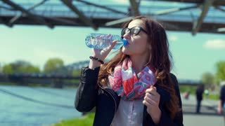 Pretty girl standing on pathway and drinking water from a bottle