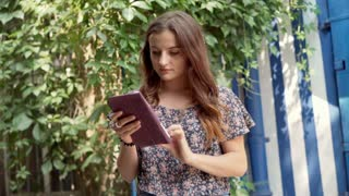 Pretty girl standing outside and browsing internet on tablet