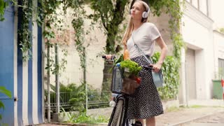 Pretty girl standing with bicycle and listening music on headphones