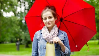 Pretty girl standing with red umbrella in the park and smiling to the camera