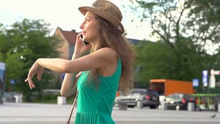 Pretty girl talking on cellphone in town, steadycam shot, slow motion shot at 24