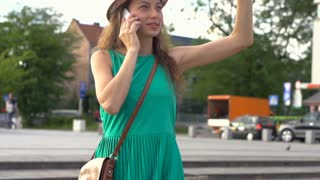 Pretty girl talking on cellphone in town, steadycam shot, slow motion shot