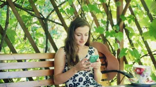 Pretty girl texting on smartphone while sitting on the bench in the arbor