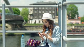 Pretty girl using smartphone and drinking water while sitting next to the river
