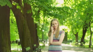 Pretty girl walking on path in the park and chatting on cellphone