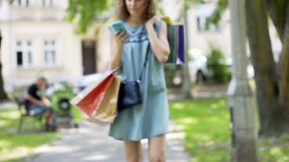 Pretty girl walking with shopping bags and using smartphone in the park