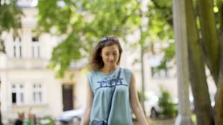 Pretty girl walking with shopping bags in the park and smiling to the camera