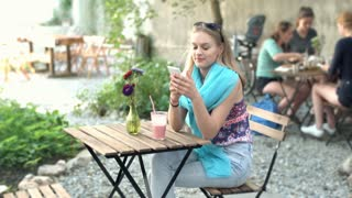 Pretty girl wearing blue scarf and texting on smartphone in the outdoor cafe