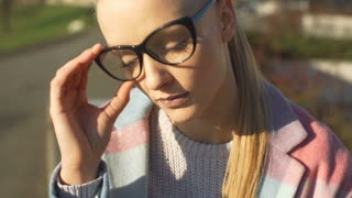 Pretty girl wearing glasses and looking pensive, steadycam shot