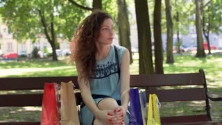 Pretty girl with curly hairs sitting with her shopping on the bench and looking