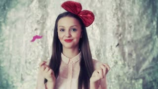Pretty girl with red bow playing with moustache and smiling to the camera