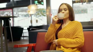 Pretty girl wrapped in yellow sweater drinking beverage and sitting in the cafe