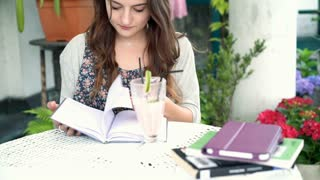 Pretty, romantic girl looking on her journal and smiling to the camera, steadyca