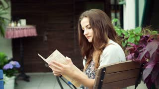 Pretty, romantic girl sitting on the wooden chair in the cafe and reading menu