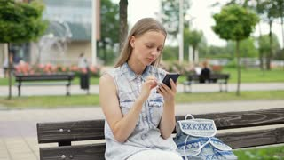 Pretty schoolgirl sitting on wooden bench and browsing internet on smartphone