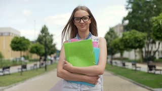 Pretty student holding colorful folders and smiling to the camera