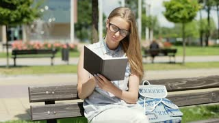 Pretty student reading book on the bench and smiling to the camera