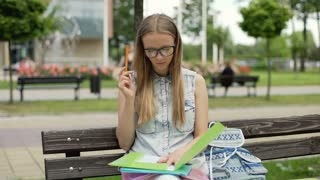 Pretty student sitting on wooden bench and doing her homework