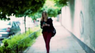 Punk girl walking on pathway and texting message on smartphone
