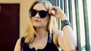 Punk girl wearing stylish sunglasses and looking to the camera