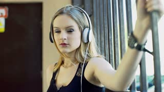 Punkg girl listening music on headphones and doing serious look to the camera