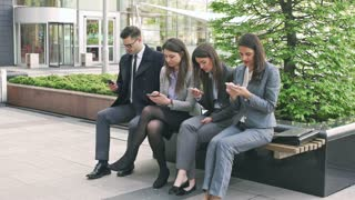 Quiet businesspeople sitting on the bench and using smartphones
