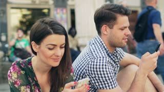 Quiet couple sitting in the city and using smartphones